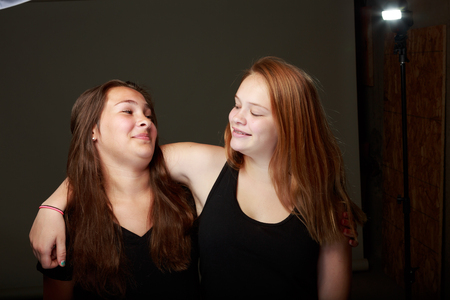 behind the scenes: Behind the scenes outtake shot of two young teenange girls posing on a grey background with lighting exposed Stock Photo