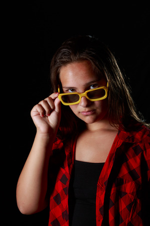 grundge: Low key studio shot of a grundge teen girl with a pair of yellow sunglasses Stock Photo