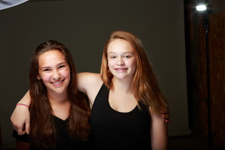 behind the scenes: Behind the scenes studio shot of two young teenange girls posing on a grey background with lighting exposed