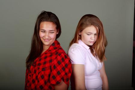 spat: Studio set of two teenange girls back to back fighting and making up