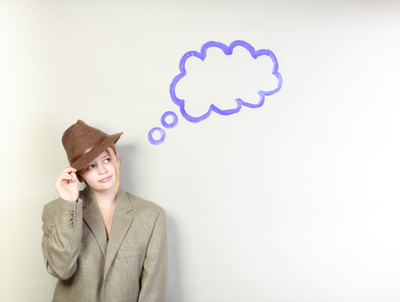suite: Studio shot of a teenange girl with a thought bubble thinking wearing a suite jacket and a fedora Stock Photo