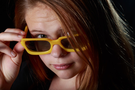 grundge: Low key studio shot of a teen girl with a pair of yellow sunglasses Stock Photo