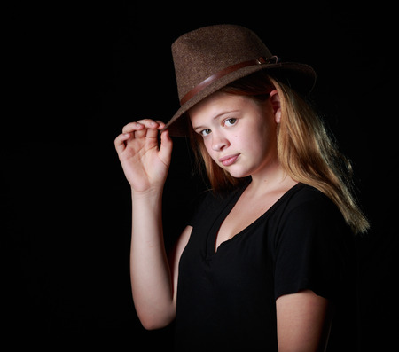 fedora: Teen Girl with a fedora on black background Stock Photo
