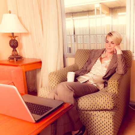 Young blonde businesswoan working in a budget hotel room in a business suite