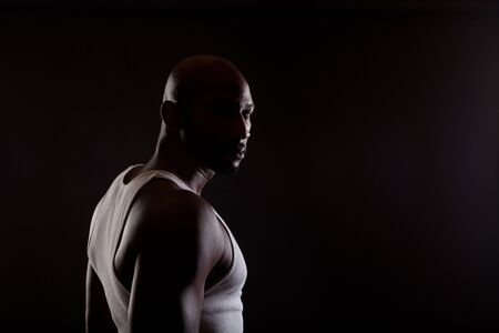 Strong contrast shot of  a young, handsome, muscular black man in shadows.