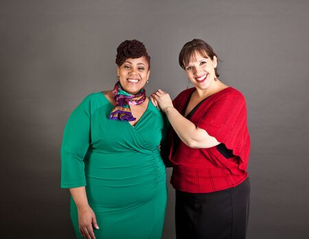 Happy, smiling plus size women of different races looking at the camera wearing bold colors