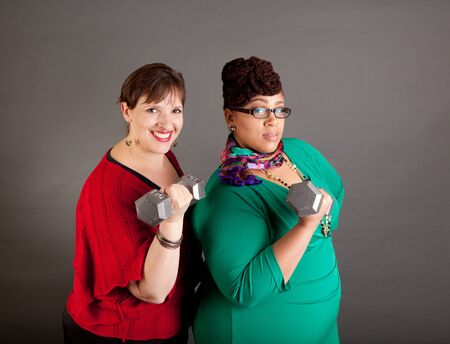 Confident, serious plus size women of different races looking at the camera wearing bold colors holding barbells denoting business power