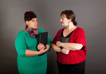 Two confident plus size business women staring at each other with tension in their faces Stock fotó
