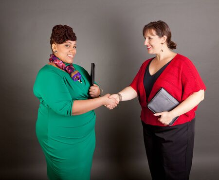 Happy, smiling plus size women of different races shaking hands holding business portfolios Stock fotó