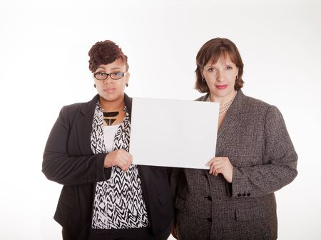 Two confident plus size mixed race business women on a white background in a happy or silly pose part of a series