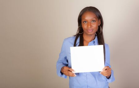 African American woman with American Indian heritage acting as a spokesperson holding a sign with room for copy. Part of a series.