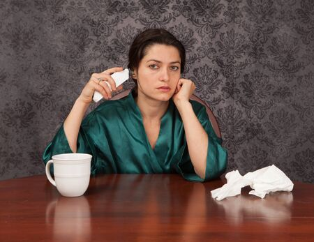 Woman suffering from headache and flu symptoms at home with a coffee cup and tissues taking her temperature Stock Photo