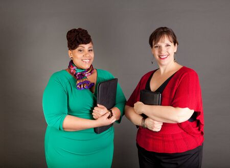 Happy, smiling plus size women of different races looking at the camera wearing bold colors holding traditional business portfolios