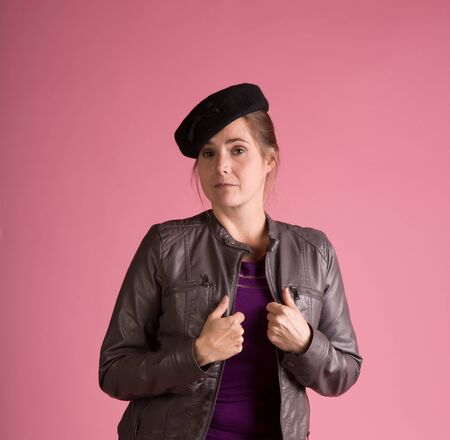 Nice shot of a woman mixing a vintage hat with a moden outfit on a pink background