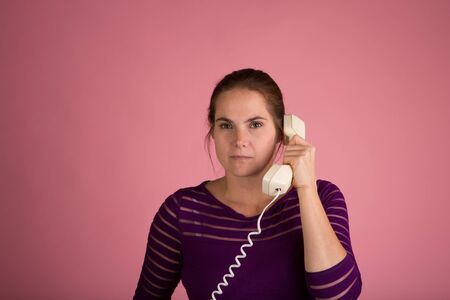Studio shot of a woman on a pink background with a vintage corded phone having a conversation