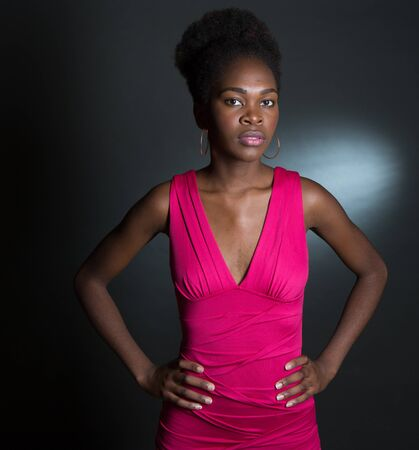 Nice Studio shot of a 20 year old African American girl with a pink dress and hands on her hips