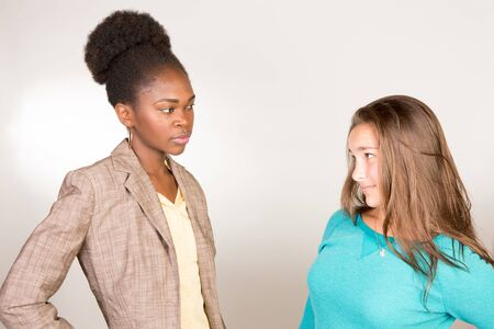 Studio shot of a young black teacher with her teen student