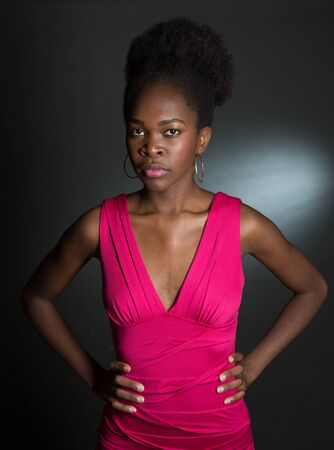 Nice Studio shot of a 20 year old African American girl with a pink dress with an attidude and hands on her hips Banco de Imagens