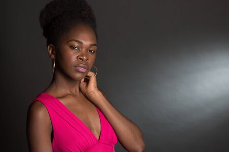 Nice Studio shot of a 20 year old African American girl with a pink dress looking shy