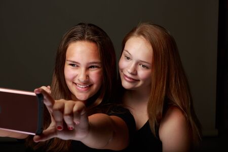 Studio set of two young teenange girls posing on a grey for a selfie