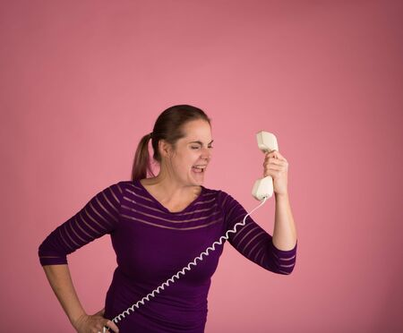 Studio shot of a woman on a pink background with a vintage corded phone having an angry conversation Archivio Fotografico