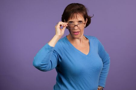 Studio set of a middle age woman adjusting her glasses and making a face on a purple background. Stock fotó
