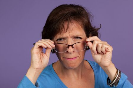 Studio set of a middle age woman adjusting her glasses and making a face on a purple background. 免版税图像