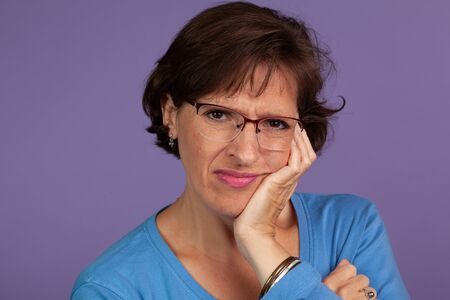 Studio set of a middle age woman adjusting her glasses and making a face on a purple background. Stok Fotoğraf