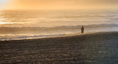 Lone surf fisherman on the beach in the early morning with mist in the air