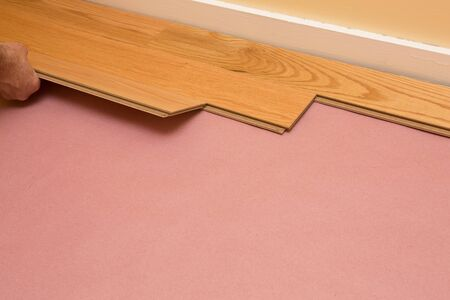 Series of shots of engineered hardwood floor being installed by a worker over pink felt paper using hand tools Banco de Imagens