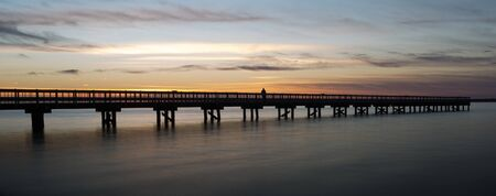 Sunset shot looking west over the Barnegat Bay in New Jersey with a fishing pier silhouetted in the foreground 免版税图像