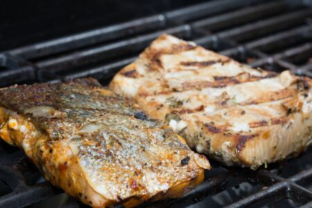 Grilling Omega3 rich salman and mahi on an outdoor gas grill for a healthy protien meal