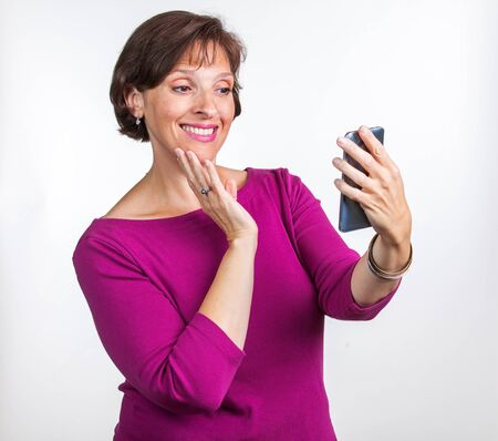 Middle Aged woman taking a selfie. Gen X social media concept image