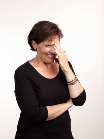 Middle age woman making a pained expresison with hand to her brow. Negative or shocked emotion concept.