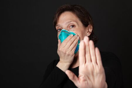 Stay Back - Woman with hospital grade mask with hand up keeping people away from her Stock Photo