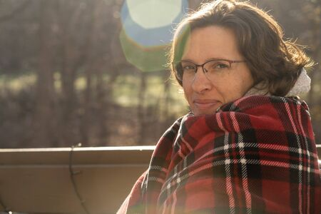 Woman wrapped in red plaid blanket outside in early morning with sunflare.