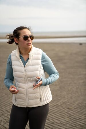 Caucasian Woman on a beach with phone in hand, looking at something with a concerned face.