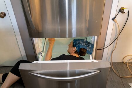 Woman working on a home refrigerator freezer