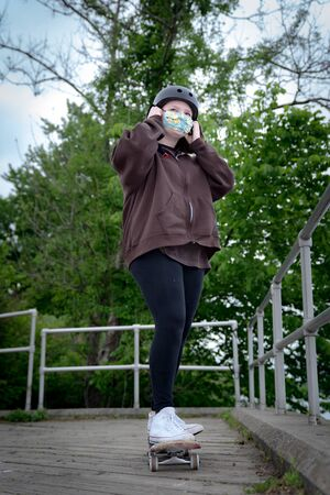 Teen girl skateboarding with a facemask