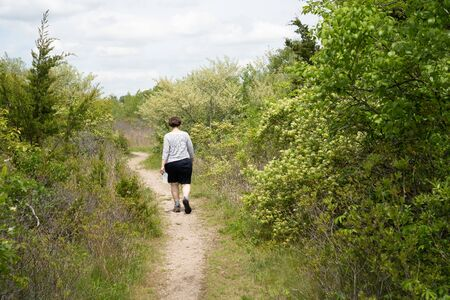 Woman walking in the woods on a trail