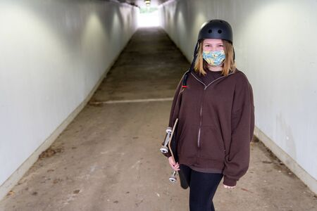 Teen Girl walking through a tunnel with her skateboard