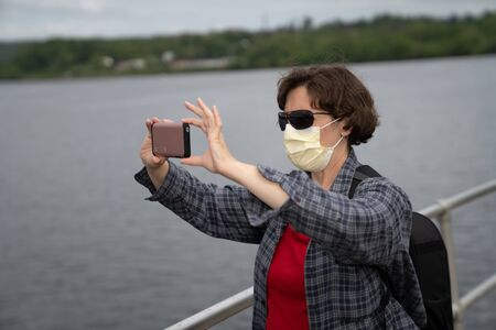 Woman with a mask taking a selfie during COVID
