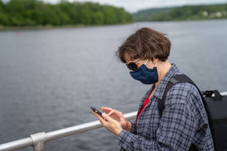 Woman with a mask using a phone during COVID Reklamní fotografie