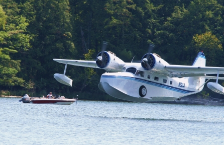 Fifield, Wisconsin - September 6, 2006:  A restored, WWII-era Grumman Goose seaplane lifts off from a lake near Fifield, WI, September 6, 2006. Stock Photo - 18740034