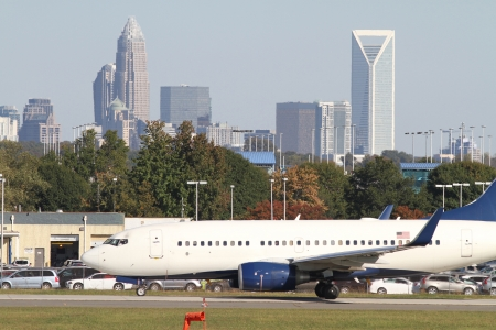 Charlotte, North Carolina - October 21, 2012: A commercial jet sits on a runway at Charlotte-Douglas International Airport with the skyline of Charlotte, North Carolina, in the background.