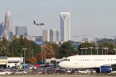 Charlotte, North Carolina - October 21, 2012: A commercial jet sits on a runway of Charlotte-Douglas International Airport while a second jet approaches with the skyline of Charlotte, North Carolina, in the background. 新闻类图片