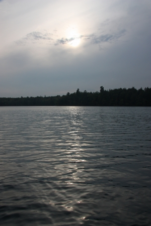 Hazy sun reflected in the rippled waters of a lake Stock Photo