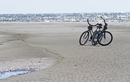 Two bicycles parked on an ocean beach 免版税图像