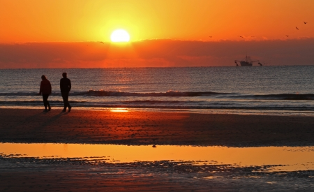 A couple walks along a beach at sunrise photo