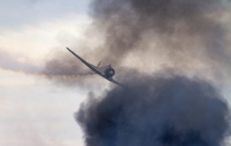 MONROE, NC -- NOVEMBER 8, 2014:  Heat from explosions below distort an aircraft participating in a reenactment of the Japanese Attack on Pearl Harbor during the Warbirds Over Monroe Air Show in Monroe, NC.
